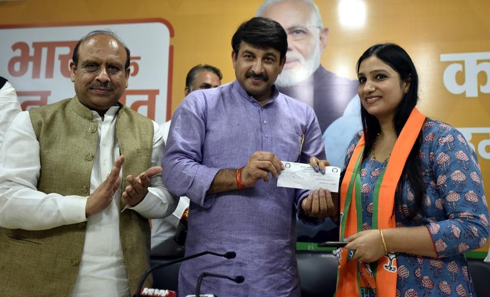 Delhi BJP President Manoj Tiwari presents a membership slip to Professor Shafali during an event where a large number of professionals joined BJP .