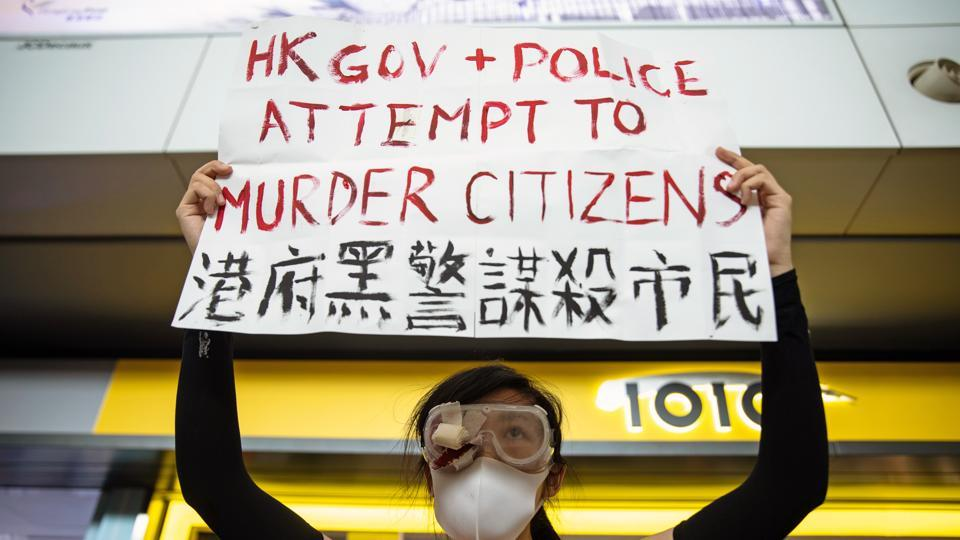 "A demonstrator holds a placard during a protest at the Hong Kong International Airport in Hong Kong, China, on August 12, 2019. ""Protesters have been frequently using extremely dangerous tools to attack the police in recent days, constituting serious crimes with sprouts of terrorism emerging,"" said Hong Kong and Macau Affairs office spokesman Yang Guang in Beijing. (Kyle Lam / Bloomberg)"