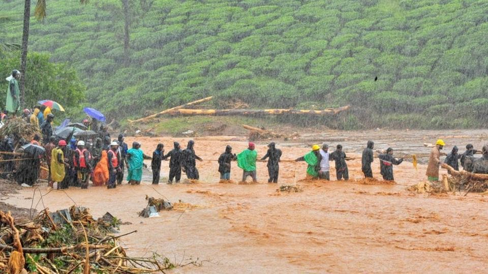 Rescuers help people cross a flooded area after a landslide caused by torrential monsoon rains in Meppadi in Wayanad district in Kerala.