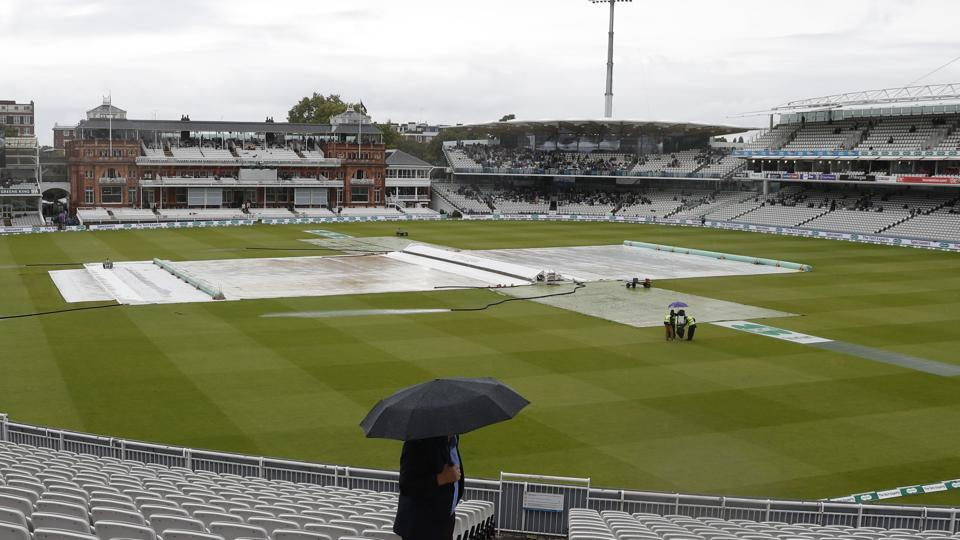 A spectator looks at the field of play that is covered to protect the wicket from rain.