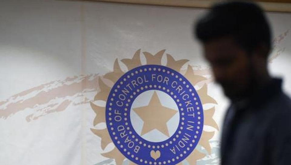 A man walks in front of the logo for the Board of Control for Cricket in India (BCCI).