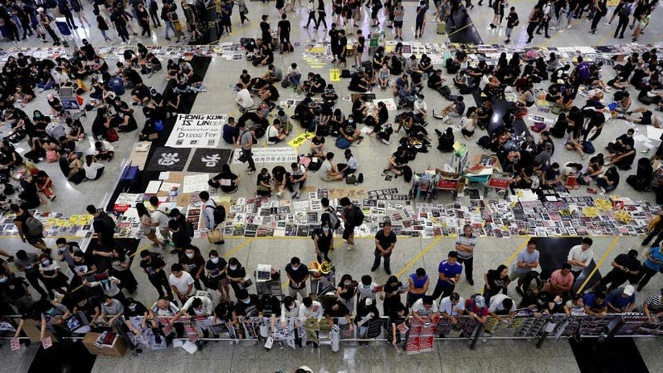 Anti-Extradition bill protesters distribute leaflets to passengers during a mass demonstration at the Hong Kong international airport, in Hong Kong.