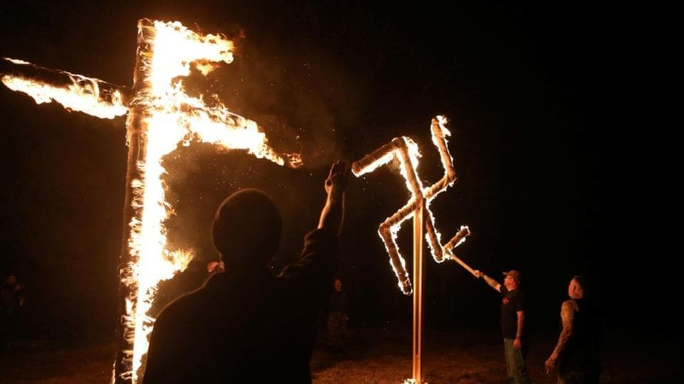 Members of the ShieldWall Network, a white nationalist group, burn a swastika and cross during a party outside Atkins, Arkansas, US. After a number of attacks on minorities, the white supremacists in the US are trying to 'normalise' these attacks. The normalization effort includes softened rhetoric and social gatherings that, for many groups, would increasingly replace confrontational rallies. (Jim Urquhart / REUTERS)