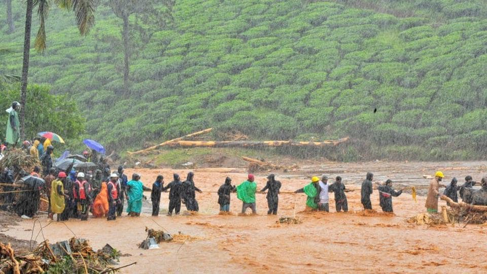 Rescuers help people to cross a flooded area after a landslide caused by torrential monsoon rains in Meppadi in Wayanad district in the southern Indian state of Kerala, India, August 9, 2019.