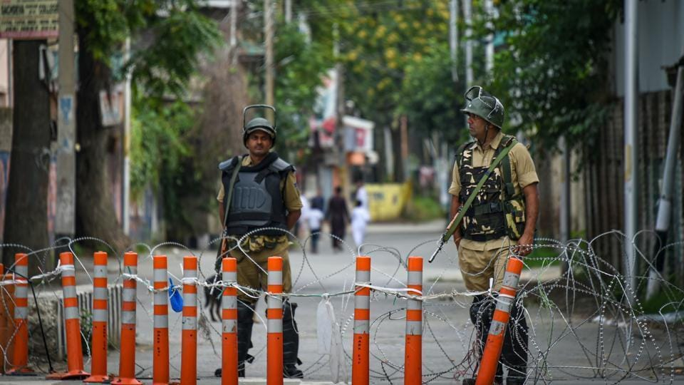 Security personnel stand guard during restrictions in Srinagar on August 12.