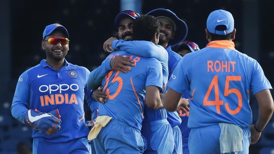 India bowler Bhuvneshwar Kumar, center, is hugged by captain Virat Kohli after catching and bowling out West Indies batsman Roston Chase.