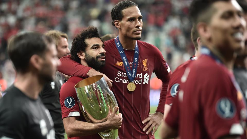Liverpool's Egyptian midfielder Mohamed Salah and Liverpool's Dutch defender Virgil van Dijk pose with the trophy.