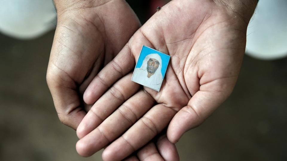 Irshad Khan, 24, holds a picture of his late father Pehlu, 55, in Jaisinghpur. The 92-page judgment, which highlights the glaring holes in the investigative process and the prosecution's case, was delivered by additional district judge Sarita Swami.