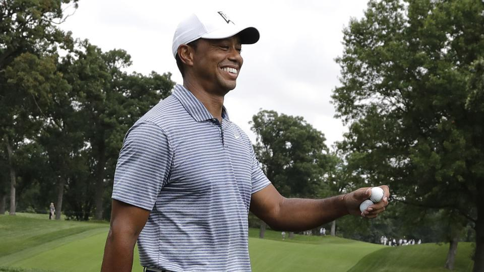 Tiger Woods smiles as he leaves the 14th green during the pro-am round of the BMW Championship golf tournament at Medinah Country Club.