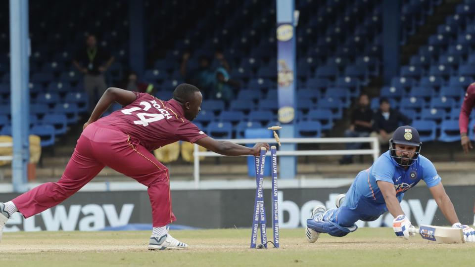 India's Rohit Sharma, right, is run out by West Indies' Kemar Roach for 10 runs during the third One-Day International cricket match in Port of Spain, Trinidad, Wednesday, Aug. 14, 2019.
