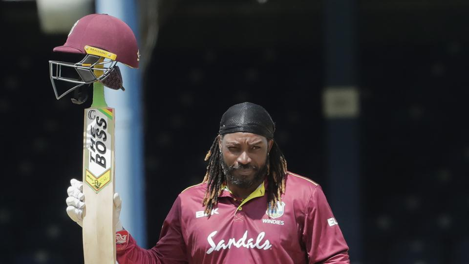West Indies opener Chris Gayle raises his bat to the crowd after reaching a half century during the third One-Day International cricket match India in Port of Spain.