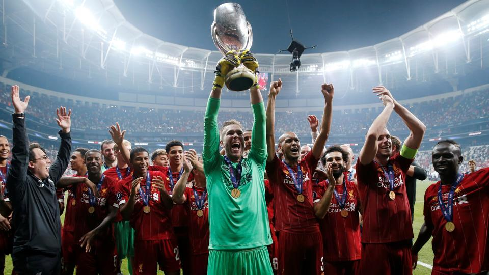 Liverpool's Adrian lifts the trophy as he celebrates winning the UEFA Super Cup with team mates.
