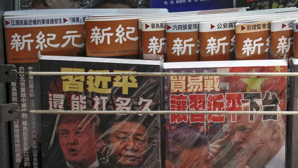 In this July 4, 2019, photo, Chinese magazines with front covers featuring Chinese President Xi Jinping and U.S. President Donald Trump on trade war are placed for sale at a roadside bookstand in Hong Kong.