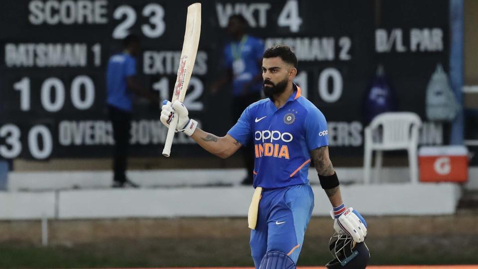 Virat Kohli raises his bats to celebrate reaching his century.