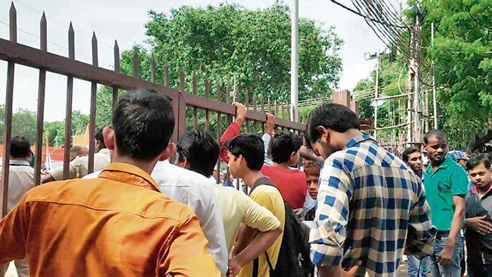 People wait outside the Red Fort premises after being stopped by the security personnel.