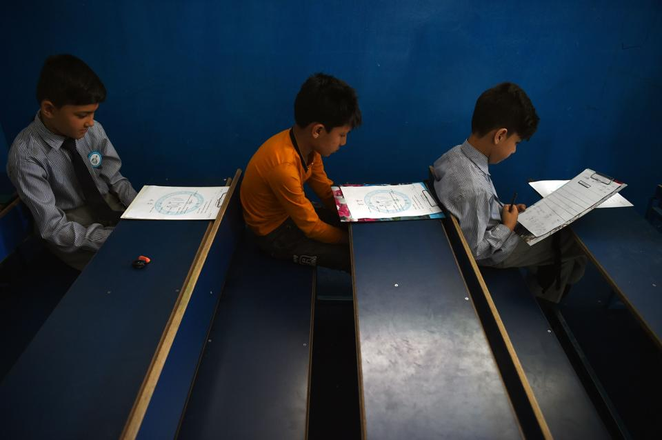 Afghan students take mid-term exams at a school in Kabul. The US and Taliban claim progress in ongoing peace talks, but little has changed for Afghans, and recent attacks underscore how children remain as vulnerable as ever in the grinding conflict. (WAKIL KOHSAR / AFP)