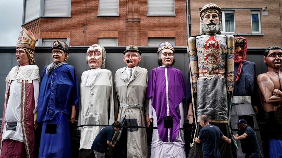 Members of the group 'The Carriers of the Giants of the Province of Liege' prepare giant puppets for a folk parade in Outremeuse, Belgium, during Assumption Day celebrations. (Kenzo TRIBOUILLARD / AFP)