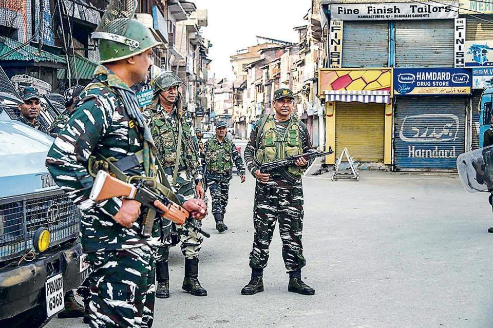 Security personnel stand guard in Srinagar on Friday.