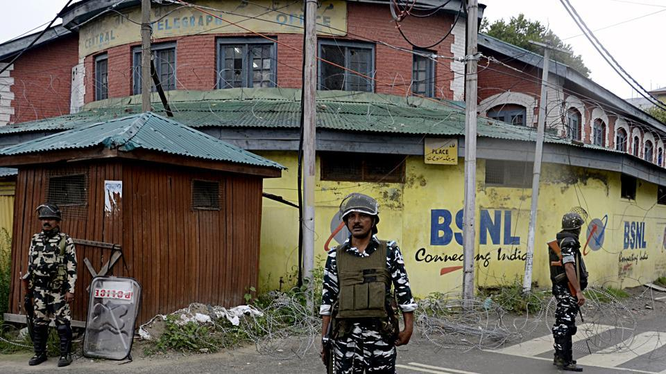 Security personnel stand guard on the street of Srinagar on Saturday.