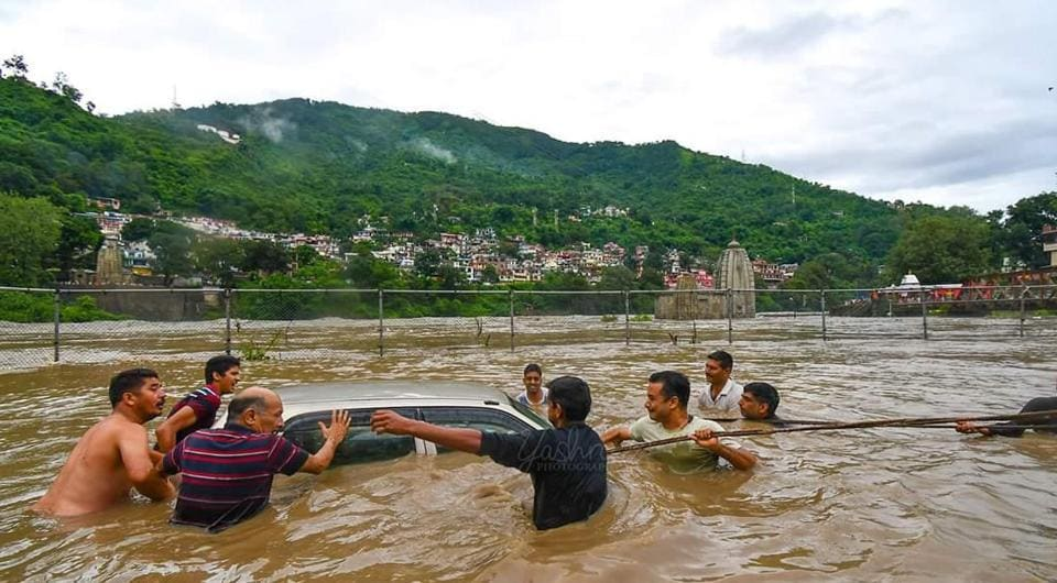 People push a submerged car in the flood waters of the Beas river in Mandi, Himachal Pradesh on Sunday.