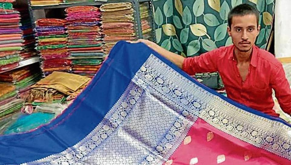 A shopkeeper in Varanasi displays a banarasi saree.