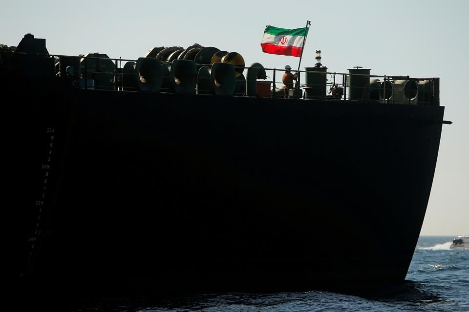 A crew member raises the Iranian flag on Iranian oil tanker Adrian Darya 1, previously named Grace 1, as it sits anchored after the Supreme Court of the British territory lifted its detention order, in the Strait of Gibraltar.