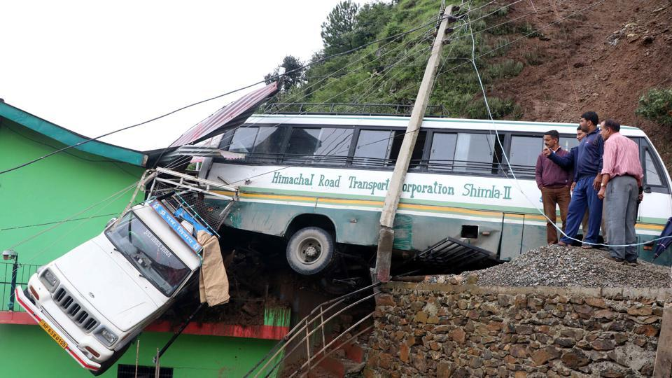 A parked HRTC bus and Bolero Camper were hit by debris after a massive landslide and pushed towards a road side building due to heavy rain near Mehli, in Shimla. As of Sunday evening, rain-related incidents had claimed at least 30 lives in Himachal Pradesh, four in Uttarakhand while dozens were reported injured. (Deepak Sansta / HT Photo)