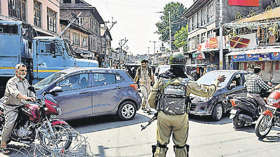A CRPF personnel stops vehicles near a temporary barricade set up by police during restriction in downtown area of Srinagar on Friday, August 16, 2019.