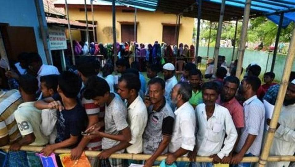 People wait in queue to check their names on the draft list at the National Register of Citizens (NRC) centre at a village inAssam.