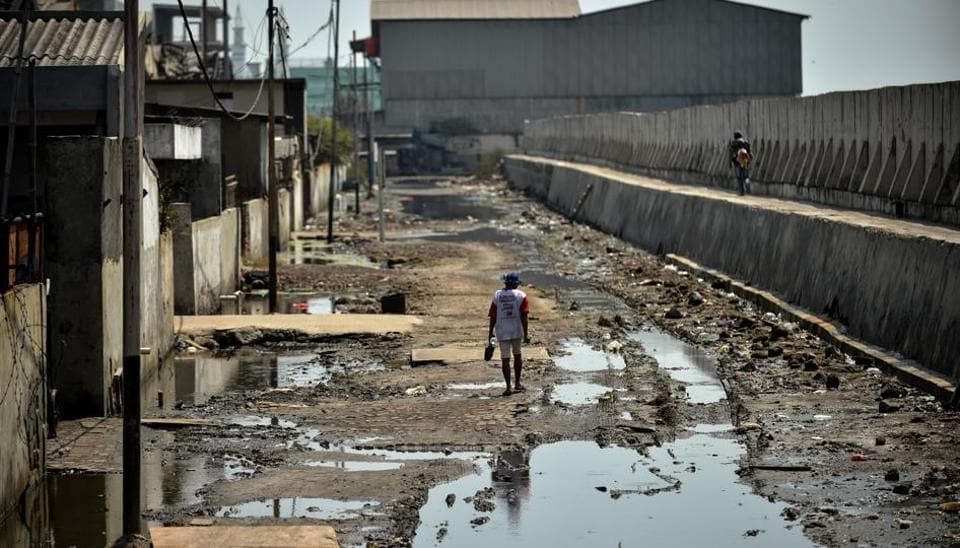 A man walks on a muddy road between abandoned warehouses and a giant sea wall in northern Jakarta. Being one of the fastest-sinking cities on earth, environmental experts warn that one third of it could be submerged by 2050 if current rates continue. Decades of uncontrolled and excessive depletion of groundwater reserves, rising sea-levels, and increasingly volatile weather patterns mean swathes of it have already started to disappear. (BAY ISMOYO / AFP)