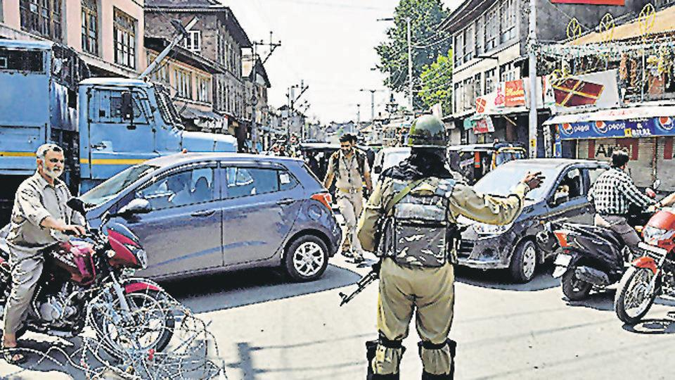 CRPF personnel stops vehicles near a temporary barricade set up by police during restriction in downtown area of Srinagar on Friday. (ANI photo)