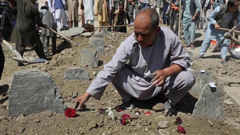 An Afghan man put flowers on a grave of his relative during a mass funeral after a suicide bomb blast at a wedding in Kabul, Afghanistan .