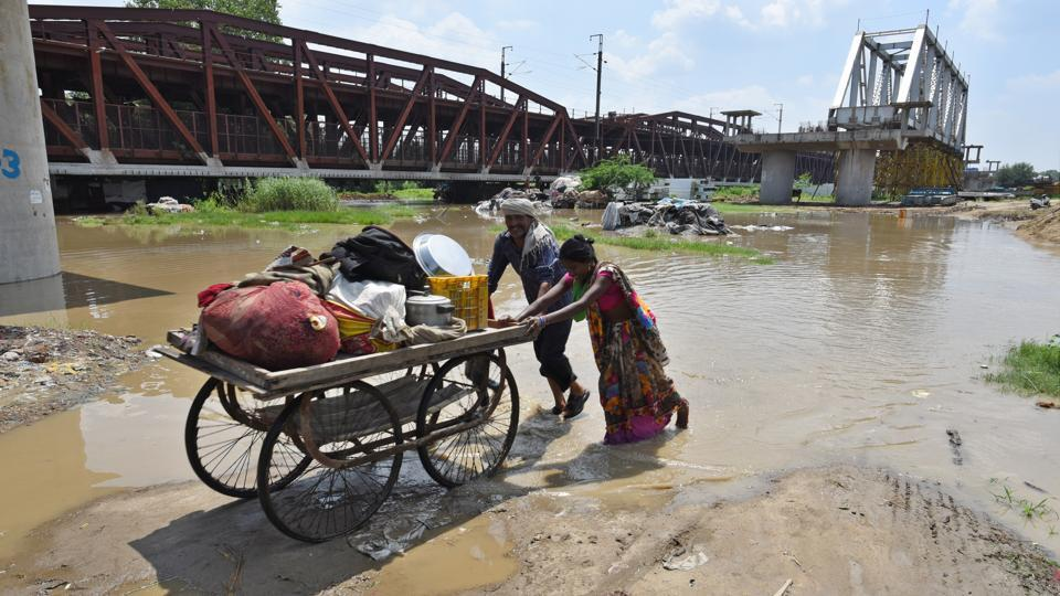 People take their belongings on a cart after their houses were submerged by the rising waters of the Yamuna River at Old Iron Bridge in New Delhi.  The water level in the Yamuna continued to rise on Tuesday and is expected to touch a maximum height of 207.08m by Wednesday afternoon, officials of the flood and irrigation department said. The water level in the river had last breached the 207m mark during the 2013 floods, when it touched 207.32m. (Sanchit Khanna / HT Photo)