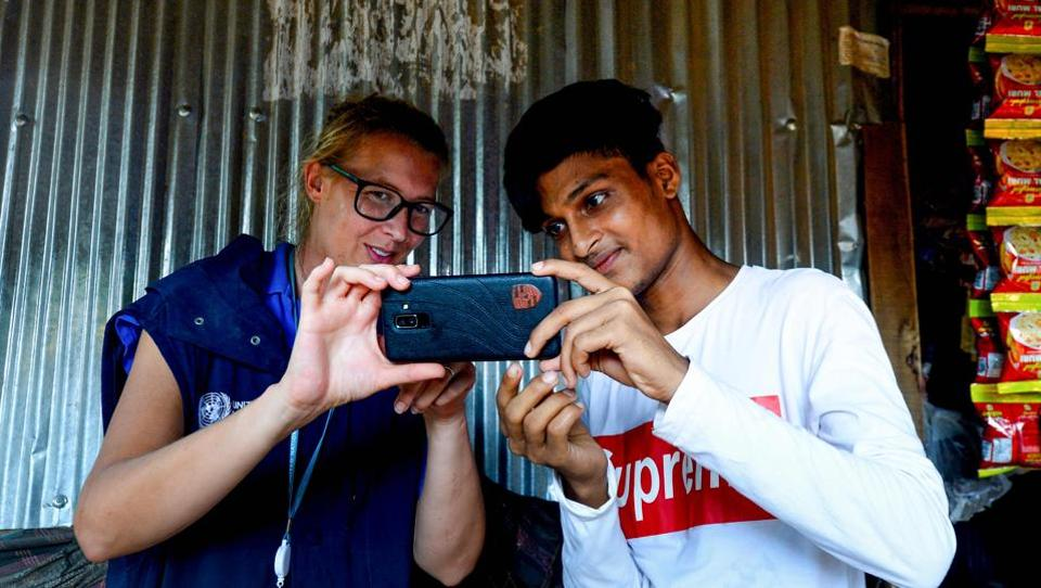 World Food Programme (WFP) official Gemma Snowdon (L) coaches Rohingya youth Mohammad Rafiq on methods to take better photos with his mobile phone at the Kutupalong refugee camp. The 19-year-old budding photographer, who fled to Bangladesh in August 2017 after a military crackdown in Myanmar, uses his mobile phone to record the daily lives of nearly one million stateless Rohingya in a vast camp in southern Bangladesh. (Munir UZ ZAMAN / AFP)