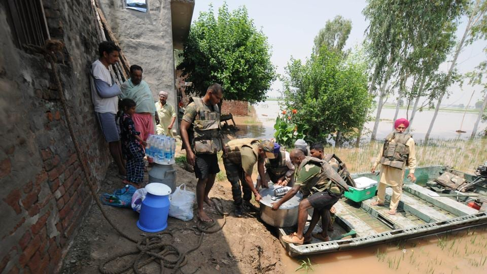 Army personnel carry food for villagers affected by severe floods, at Jamaliwala Village, in Punjab.