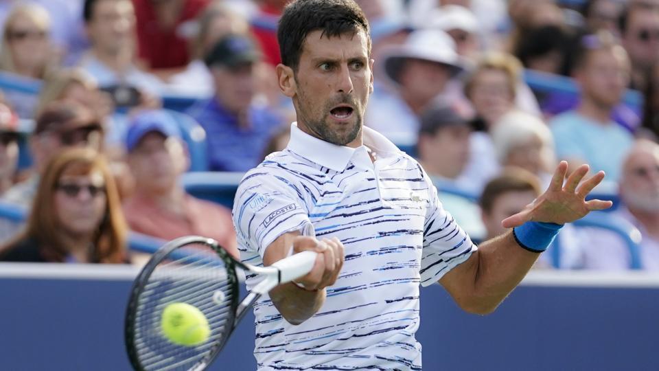 Novak Djokovic, of Serbia, hits a forehand to Daniil Medvedev, of Russia.