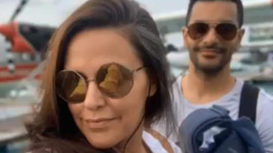 Neha Dhupia happily poses for the camera as Angad Bedi smiles.