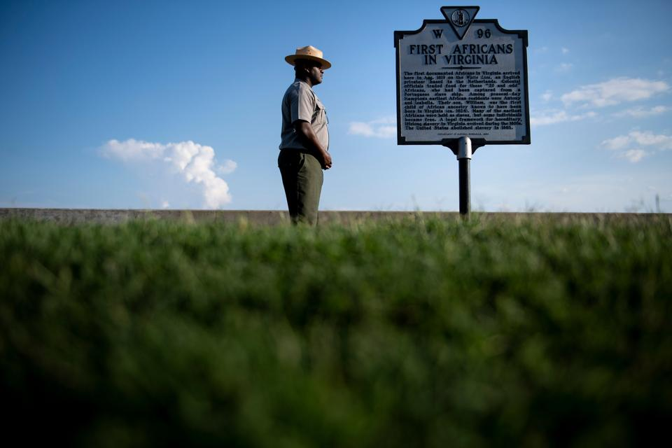 """Superintendent of Fort Monroe National Monument, Terry E. Brown, is seen near a historical marker at the fort, in Hampton, Virginia. Brown and his team are preparing a series of events on August 23-25 to celebrate the """"contributions"""" of Africans to US society. """"The more we gather around, the more we talk, the easier it is to break with the insidiousness of racism,"""" said Brown, who discovered through a DNA test that his ancestors came from Cameroon.  (Brendan Smialowski / AFP)"""