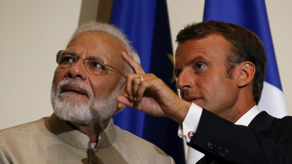 French President Emmanuel Macron, right, gestures next to Indian Prime Minister Narendra Modi after a joint press conference at the Chateau de Chantilly, north of Paris.