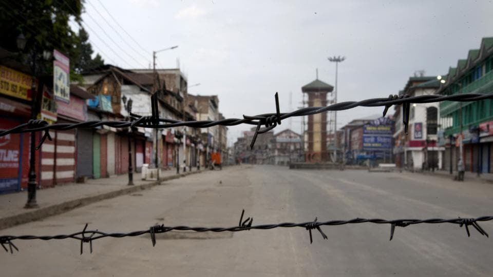 A deserted street is seen through barbed wire set up as a barricade during curfew in Srinagar. The streets of Kashmir Valley's cities and towns, often reverberating with chants, are all but empty. The region is in the third week of an unprecedented lockdown that has largely kept its 7 million residents indoors. (Dar Yasin / AP)
