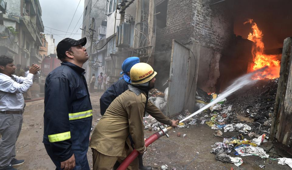 Fire fighters trying to douse the flames after fire broke out at Ahuja Enterprises at Central Market on Gill Road, Ludhiana, on Friday.