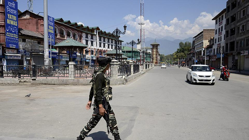 CRPF personnel stand guard in front of closed shops in Srinagar.