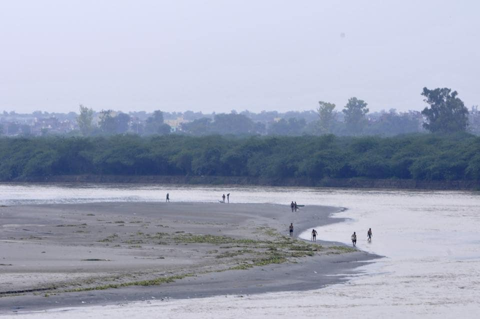 People out by the Yamuna after a recession in the water level of the river. Signboards or banners which display that throwing waste is not allowed shall be put up near lakes, warning of legal action in case of violation.