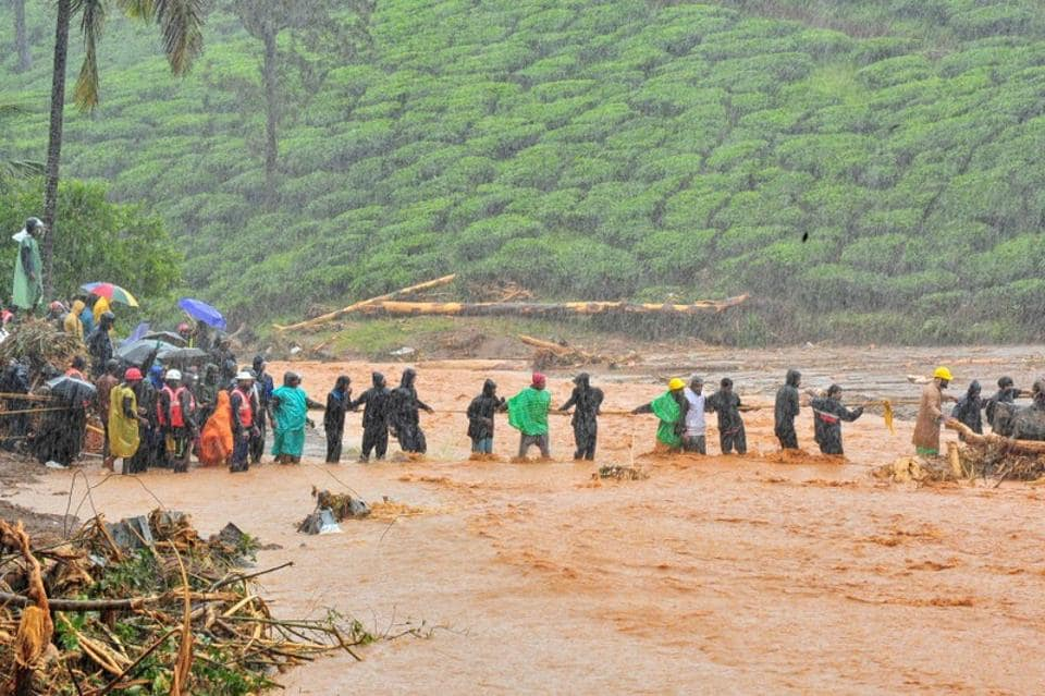 Rescuers help people to cross a flooded area after a landslide caused by torrential monsoon rains in Meppadi in Wayanad district in Kerala, August 9, 2019.