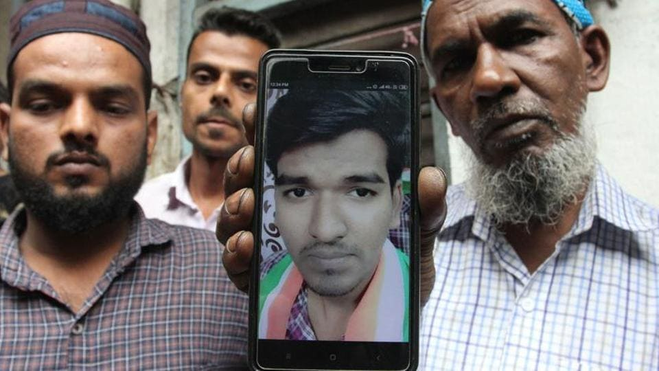 Mohammad Habib Shaikh, father of Aaqib Shaikh, holds his deceased son's photo in a cellphone.