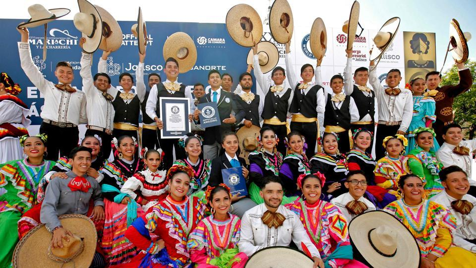 "Mariachi dancers pose with the Guinness World Record of largest Mexican folk dance in Guadalajara. ""Yes, we can!"" participants screamed with joy when the Guinness record was announced. (Ulises Ruiz / AFP)"