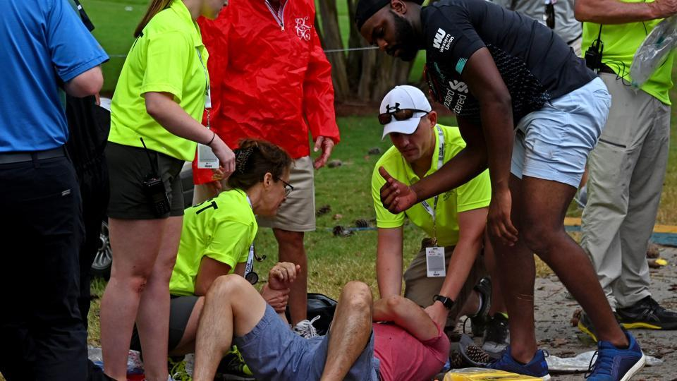 Fans are assisted by medical personnel after a lightning strike.