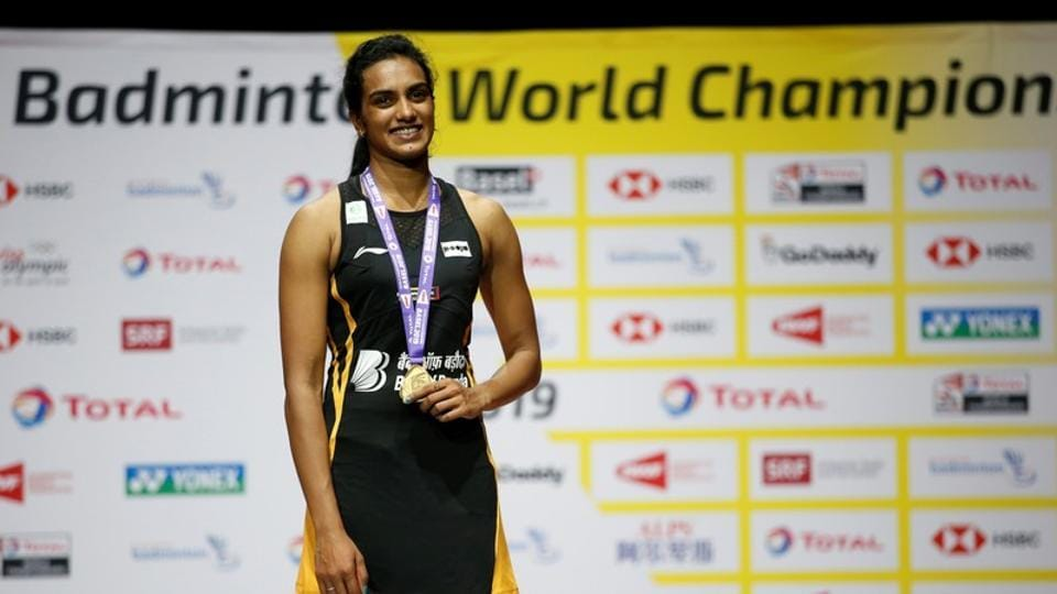 India's Pusarla Sindhu celebrates on the podium with her gold medal after winning the women's singles final in the BWF World Championships in Basel.