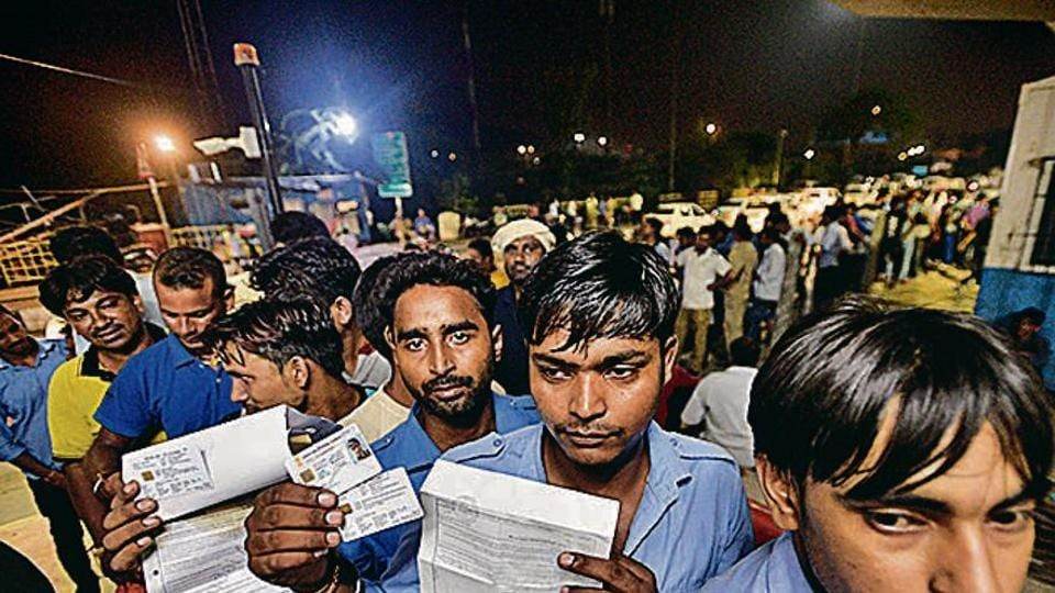 People queued to get RFID Cards at Ghazipur toll booth hold up their documents in New Delhi