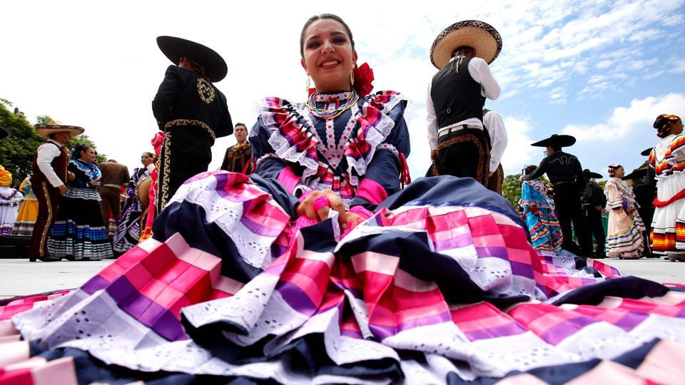 "A woman poses as the record seeking couples dance to Mariachi music. ""It is impressive to see so much coordination and such a full expression of Mexican culture, it is the best,"" spectator Karla Gallardo, 24, said. (Ulises Ruiz / AFP)"